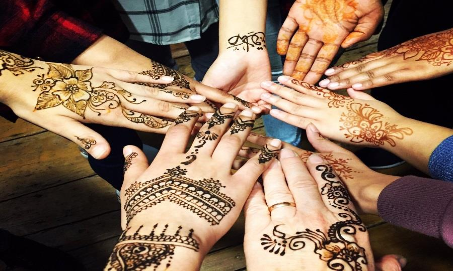 A group show off their beautiful henna at a family festival.