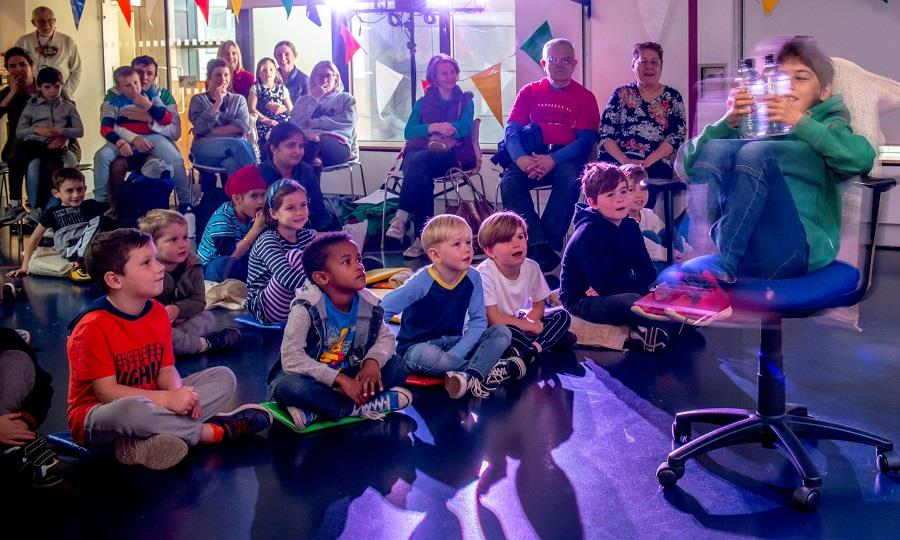 Audience watching child holding water bottles