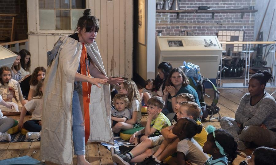 Storyteller wearing cloak telling stories to audience